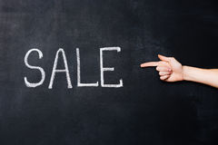 Hand die die op verkoop richten op bord wordt geschreven royalty-vrije stock fotografie