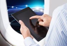 Hand die digitale tablet in vliegtuig met horizonachtergrond houden Stock Foto's