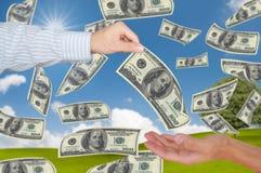 Hand die dollar 100 geeft aan een andere hand Stock Afbeeldingen