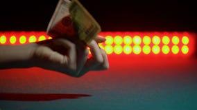 Hand die 100 dollars op stadium, concept tonen inkomens in nachtclub, close-up stock videobeelden