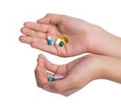 Hand, die Drogenkapsel auf weißem Hintergrund hält Lizenzfreie Stockfotos