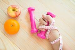Hand, die dumbell mit Maßband und Frucht hält stockfoto