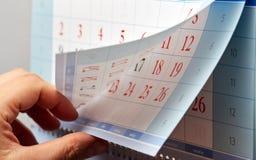 Hand, die durch Blätter des Wandkalenders leicht schlägt Lizenzfreie Stockfotos