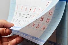 Hand, die durch einen Wandkalender leicht schlägt Stockfoto