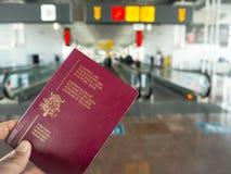 Hand die een Belgisch paspoort houden terwijl het lopen in een luchthaven stock foto