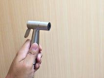 Hand die een bidetdouche op houten muur gebruiken stock foto's