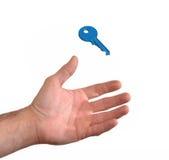 Hand die een blauwe sleutel vangen Stock Fotografie