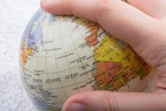 Hand die een bol met de kaart op het houden Royalty-vrije Stock Fotografie
