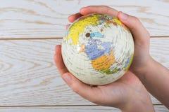 Hand die een bol met de kaart op het houden Royalty-vrije Stock Foto's