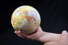Hand die een bol met de kaart op het houden Stock Foto