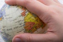 Hand die een bol met de kaart op het houden Stock Fotografie