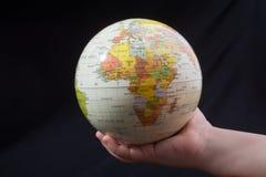 Hand die een bol met de kaart op het houden Royalty-vrije Stock Foto