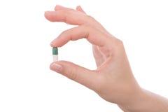 Hand die een capsule of een pil houdt Stock Afbeelding