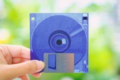 Hand die een diskette houden tegen vage achtergrond Stock Foto
