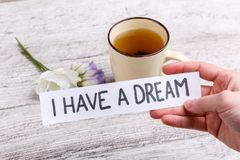 Hand die een document met een inschrijving houden heb ik een droom, tegen een lijst met een mok van zwarte thee en bloemen royalty-vrije stock afbeelding