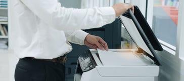Hand die een documentdocument in printerscanner of de machine van het laserexemplaar in bureau zetten stock foto