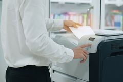 Hand die een documentdocument in printerscanner of de machine van het laserexemplaar in bureau zetten stock fotografie