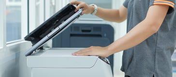 Hand die een documentdocument in printerscanner of de machine van het laserexemplaar in bureau zetten royalty-vrije stock foto