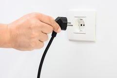 Hand die in een elektrisch koord in een contactdoos stoppen Royalty-vrije Stock Fotografie
