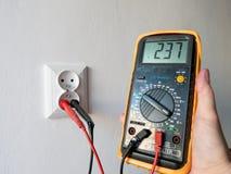 Hand die een elektrische multimeter voor de elektrische contactdoos houden stock foto