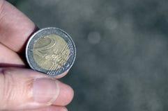 Hand die een euro muntstuk twee houden Royalty-vrije Stock Fotografie