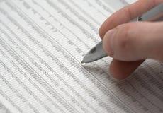 Hand die een glanzende pen over een spreadsheet houdt Stock Foto's