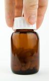 Hand die een glas van pillen grijpt Stock Foto