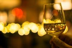Hand die een glas witte wijn met lichten op de achtergrond houden royalty-vrije stock afbeelding
