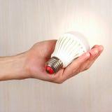 Hand die een gloeiende bol op lichte houten achtergrond houden Royalty-vrije Stock Foto