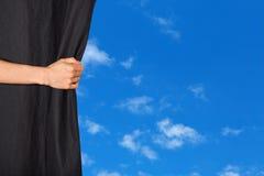 Hand die een gordijn met blauwe hemel openen achter het Royalty-vrije Stock Afbeeldingen