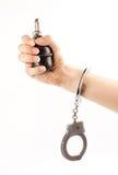 Hand die een granaat in handcuffs houdt stock afbeelding