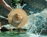 Hand die een hoed op het water houden stock afbeeldingen