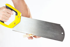 Hand die een houten blok met een handsaw op witte achtergrond snijden Royalty-vrije Stock Afbeelding