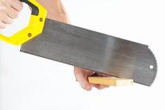 Hand die een houten blok met een metaalzaag zagen Stock Foto's