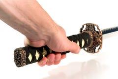 Hand die een Japans zwaard houdt Stock Foto