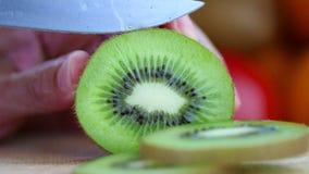 Hand die een kiwi met een mes snijden Stock Afbeeldingen