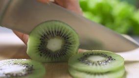 Hand die een kiwi met een mes snijden stock footage
