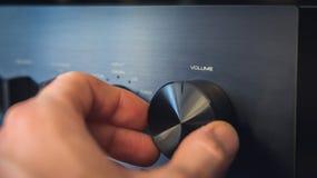 Hand die een knop met de tekst draaien die van het outputvolume op het, met het gevolg van kosten per eenheidsvermindering wordt  stock fotografie