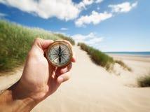 Hand die een kompas houdt Stock Foto