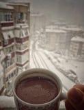 Hand die een kop van koffie houden tegen stadsmening onder sneeuw in de winter Stock Foto