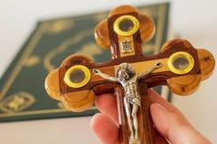 Hand die een kruis houden die de kruisiging van Jesus Christ afschilderen tegen de achtergrond van de Heilige Bijbel stock afbeelding
