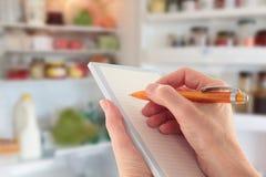 Hand die een Lijst voor een open Koelkast schrijft stock afbeeldingen
