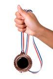 Hand die een medaille houdt Stock Afbeeldingen