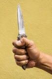 Hand die een mes op gele achtergrond houden royalty-vrije stock fotografie