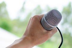 Hand die een microfoon houden Stock Foto's