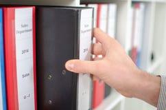 Hand die een omslag van een plank terugtrekken Royalty-vrije Stock Foto's