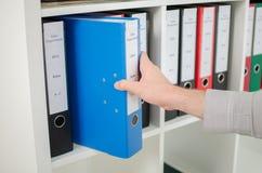Hand die een omslag van een plank terugtrekken Stock Foto