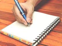 Hand die een pen houden schrijvend op het notitieboekje Stock Foto's