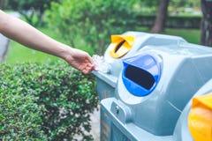 Hand die een plastic zak werpen in de bak Concepten milieu stock fotografie