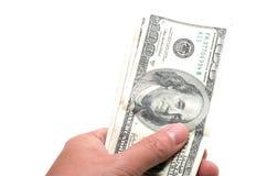 Hand die een reeks bankbiljetten met 100 dollars op bovenkant houden Stock Fotografie